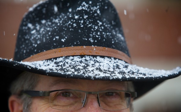 An attorney with Gross, Minsky & Mogul, P.A., Steven Mogul's hat is covered with snow as he walked across a Kenduskeag foot bridge Wednesday in Bangor. A late winter storm that started Wednesday is expected to bring as much as 2 feet of snow to parts of Maine, according to the National Weather Service.