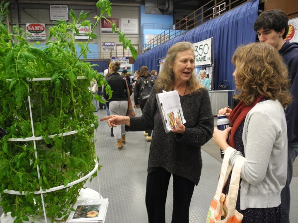 Pat Berger of Sidney shows off her low-water tower garden to Emma Enoch and Eli Cohen of Farmington, both seniors at Mount Blue High School, Wednesday at the Climate Solutions Expo and Summit at the Augusta Civic Center. &quotI'm doing a project in school. Each student has to come up with their own way to reduce climate change,&quot Enoch said. &quotThis was a really awesome way to get some new ideas. It's fantastic.&quot