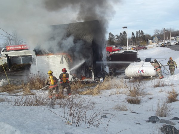 Machias firefighters battle flames at a small storage building behind the McDonald's restaurant on U.S. 1 Wednesday afternoon. The fire was brought under control in about 30 minutes.