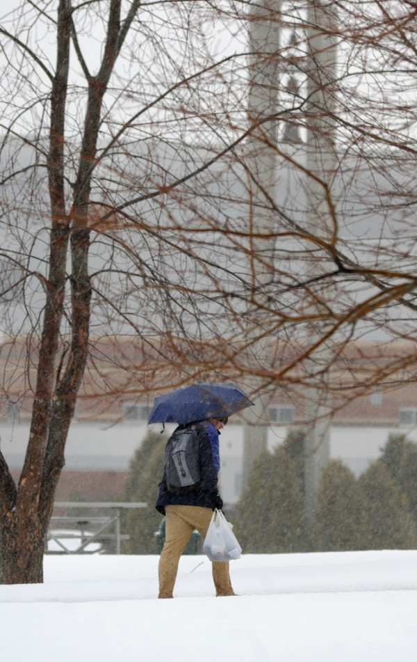 A student makes his way across the campus of Husson University during a rain shower on Thursday.  According to NOAA, today's high temperature is 43 degrees with rain showers through early afternoon.