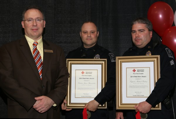 Old Town police Sgt. Michael Hashey (right) and Detective Jamie Slauenwhite (center) after receiving Real Hero Awards from the Pine Tree Chapter of the American Red Cross.