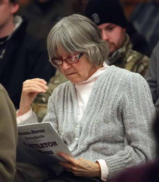 Littleton resident Patsy Hamilton checks out the town report during Monday night's annual meeting.