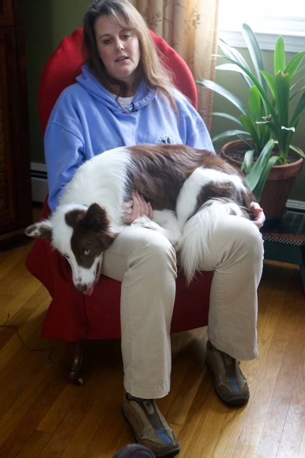 Stephanie Fox, who suffers from Lyme disease, holds her dog Roosevelt in her Portland home on Thursday.