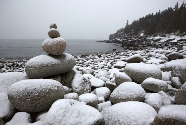 Balanced round rocks stand on the shoreline in a cove near Otter Cliffs at Acadia National Park.