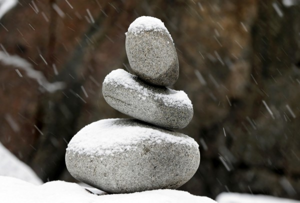 Snow accumulates on balanced rocks at Acadia National Park.