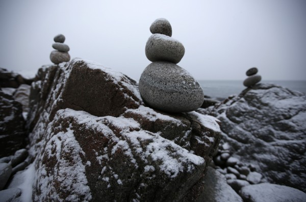 Balancing round rocks stand on the jagged rocks that dominate the coastline at Acadia National Park in Maine.