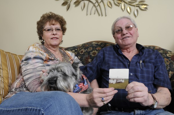 Armand and Lorraine Pelletier of Bangor sit with their dog Cody holding a picture of their home on Pelletier Road in Frenchville where they lived in 1985. Both are still haunted by the remains of a newborn that was brought lifeless to their doorstep by their Husky Paca a little over 28 years ago.