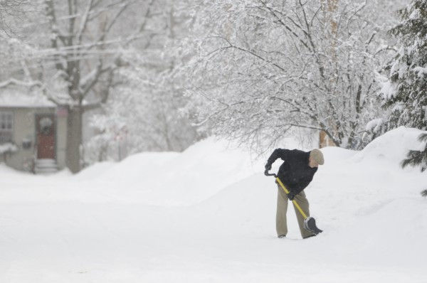 Jim Bishop shovels his drive on Fairfax Street in Bangor after a snow storm subsides on March 13.