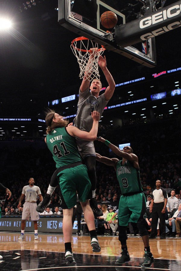 Brooklyn Nets power forward Mason Plumlee (1) is fouled as he drives to the basket by Boston Celtics center Kelly Olynyk (41) in front of Celtics point guard Rajon Rondo (9) during the third quarter of a game at the Barclays Center in Brooklyn Friday night. The Nets defeated the Celtics 114-98.