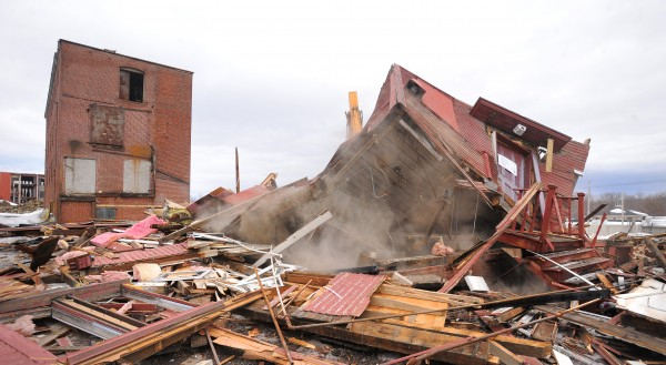 A building is demolished Friday at the former Old Town Canoe Co. site in downtown Old Town.