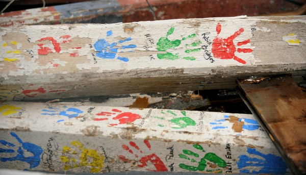 Handprints and names are visible on posts that were inside a building at the former Old Town Canoe Co. property.