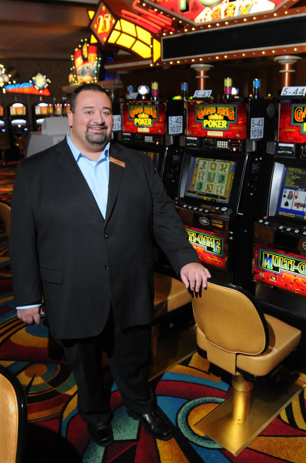 Jose Flores, the new general manager of Hollywood Casino in Bangor, stands near some slot machines on Thursday.
