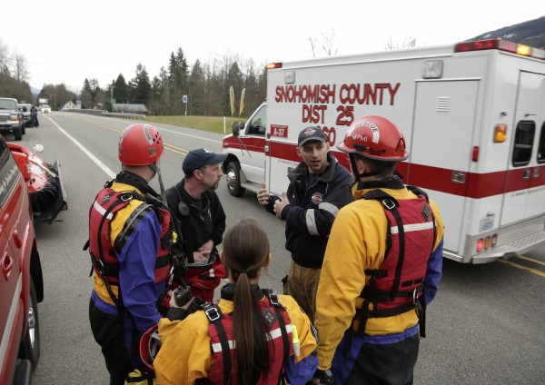 Members of a swift water rescue team huddle as an ambulance heads in the direction of a large mudslide that has blocked Highway 530 near Oso, Wash., on Saturday.