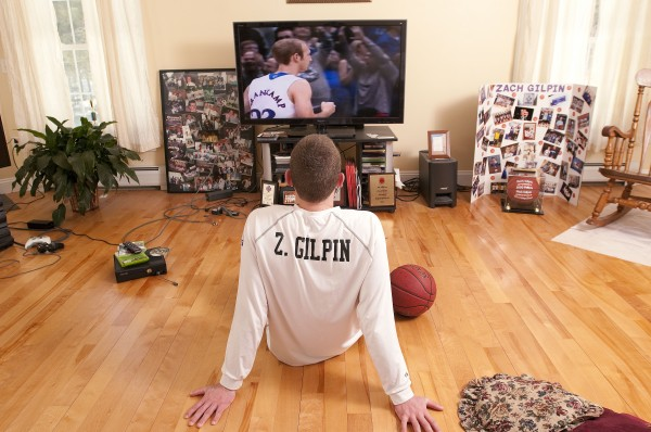 Zach Gilpin watches NCAA March Madness at his family home in Hampden on Sunday surrounded by family pictures and mementos of his high school basketball career.