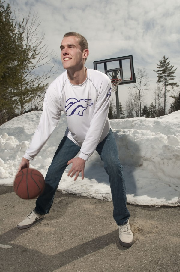 Hampden Academy's Zach Gilpin smiles while practicing some of his basketball moves outside on Sunday.