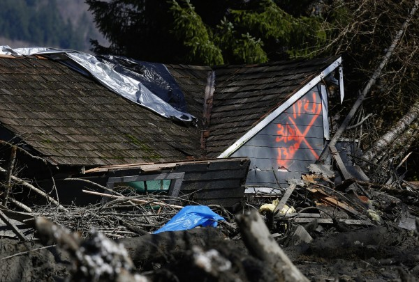 The orange X on a house, destroyed in the mud, indicates it has been searched for people on Highway 530 next to mile marker 37 on Sunday, March 23, 2014, the day after a giant landslide occurred near mile marker 37 near Oso, Washington.  At least six homes have been washed away, with three people reported dead so far and at least eighteen missing. The nearby Stillaguamish River has been dammed up by 15-20 feet of debris as a result, creating more flooding concerns, as reported by KING 5 via the state hydrologist.