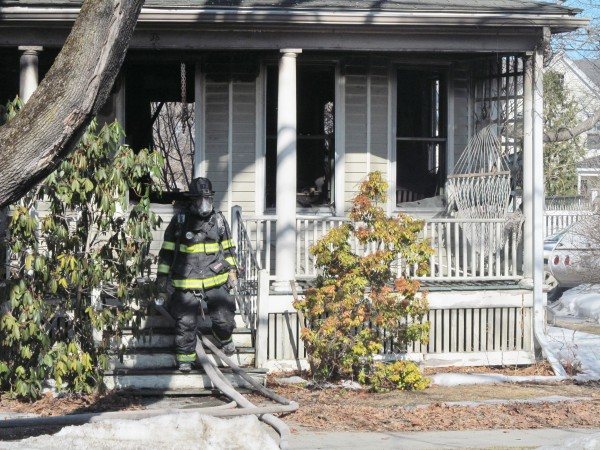 A Portland firefighter leaves a Cumberland Road residence damaged by fire Monday morning. Portland Fire Chief Jerome LaMoria said at the scene investigators were still determining a cause and damage estimate for the blaze.
