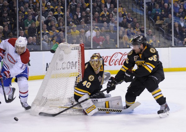 Montreal Canadiens left wing Rene Bourque (17) controls the puck behind the goal while Boston Bruins goalie Tuukka Rask and defenseman Johnny Boychuk defend during the second period at TD Banknorth Garden in Boston Monday night.