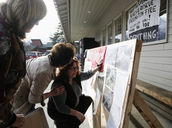 Brenda Neal (R) is consoled by Carol Massingale (2nd L) as she looks at aerial photos of a massive landslide for her missing husband's car in Darrington, Washington March 24, 2014. The confirmed death toll from a devastating weekend mudslide in Washington state climbed to 14 people on Monday as six more bodies were found, while scores of others remained listed as missing two days after the tragedy, authorities said.