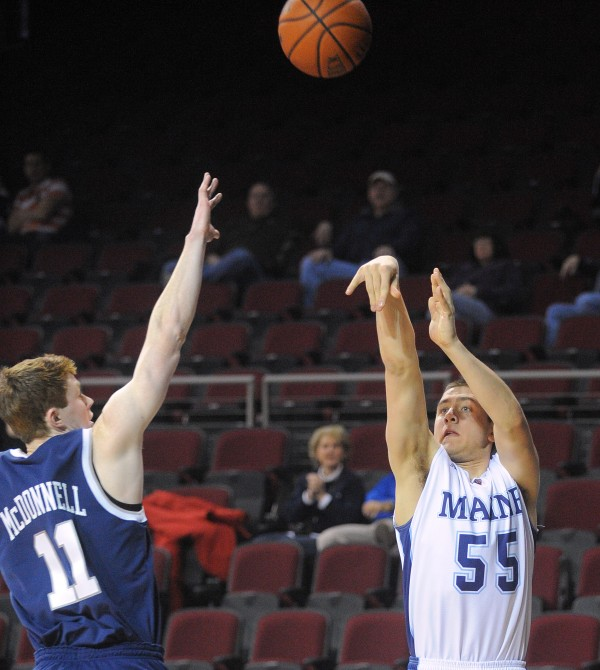 The University of Maine's Garet Beal puts up for a shot over New Hampshire's Tommy McDonnell during a game on March 2 at the Cross Insurance Center in Bangor. Beal is one of three players from the state of Maine on the team.