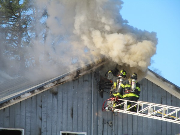 Gorham firefighters on a ladder truck use a chain saw to get access to a second-story fire at Town & Country Cabinets on Fort Hill Road Tuesday morning.