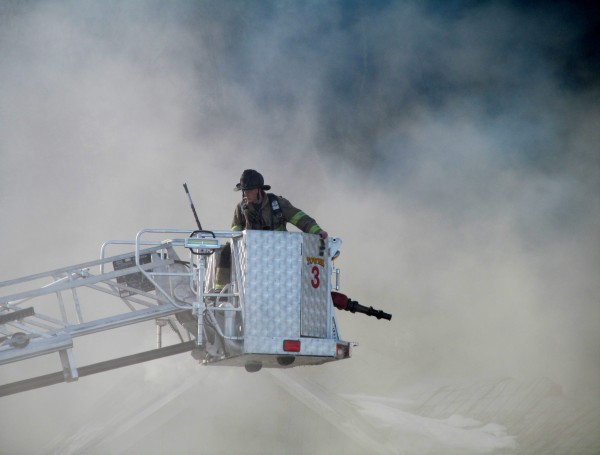 A firefighter on a Windham-based tower truck is pulled from a fresh billow of smoke Tuesday morning at the scene of a Fort Hill Road blaze.