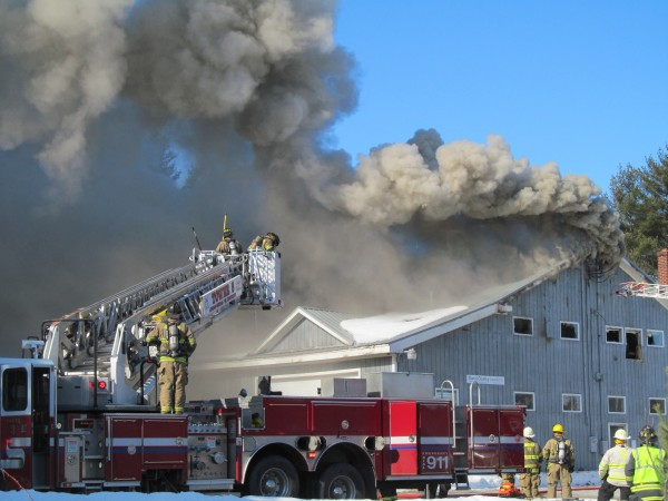 Firefighters work to contain a blaze at Town & Country Cabinets on Fort Hill Road in Gorham Tuesday morning.
