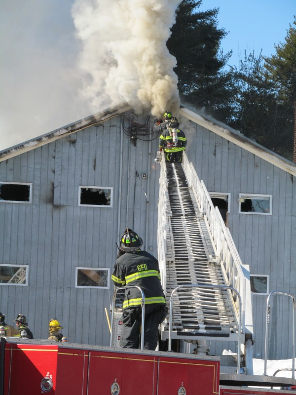 Firefighters use a Gorham ladder truck to reach the highest point in a second-story blaze on Fort Hill Road in Gorham Tuesday morning.