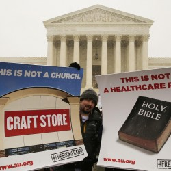 Protesters hold signs at the steps of the Supreme Court as arguments begin Tuesday to challenge the Affordable Care Act's requirement that employers provide coverage for contraception as part of an employee's health care.