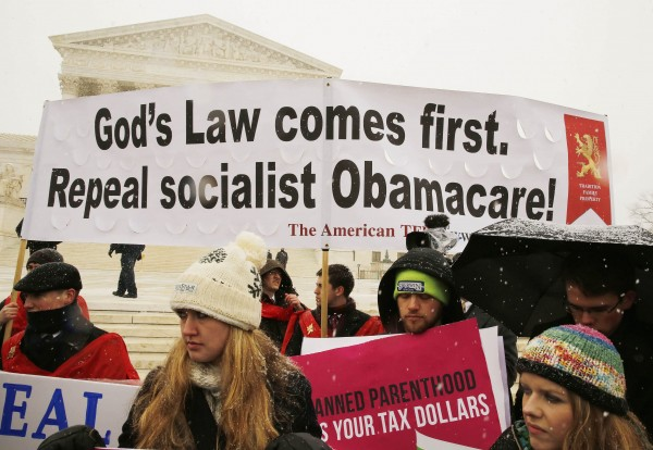 Protesters rally at the steps of the Supreme Court as arguments begin Tuesday to challenge the Affordable Care Act's requirement that employers provide coverage for contraception as part of an employee's health care.