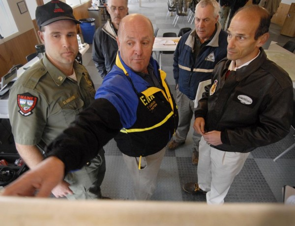 Vernon Ouellette points to a map Wednesday showing the flooded areas in Fort Kent at the command center at Lonesome Pine Trails in Fort Kent in 2008. Joining Ouellette at the command center were (from left) Maine Warden Sgt. Dan Menard, scene commander; Fort Kent Town Manager Don Guimond (background); Maine Emergency Management Agency state dam inspector Tony Fletcher; and Gov. John Baldacci.