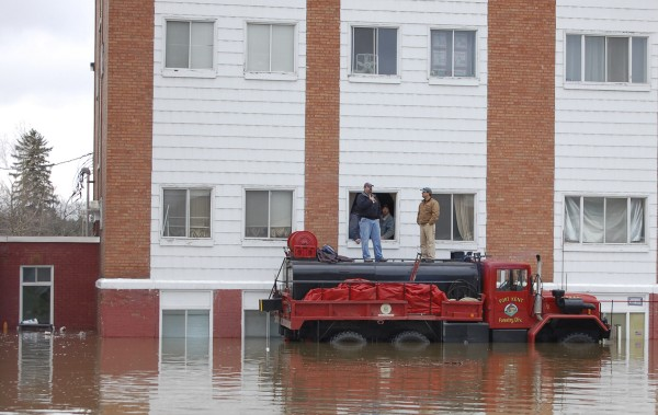 Fort Kent firefighters Curtis Saucier (left) and Michael Daigle stand atop a Fire Department tanker truck while assisting with the evacuation of the B&M Apartments on East Main Street after the Fish River spilled over its banks in downtown Fort Kent in 2008.