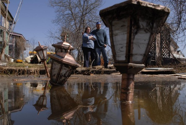 Sue Roy and her husband, James Ouellette, look at their backyard, which remained submerged on May 1, 2008. They say they were the only residents to remain in their home on East Main Street after their neighbors were evacuated earlier in the week due to the flood. &quotIt's going to be one heck of a clean-up&quot said Roy.