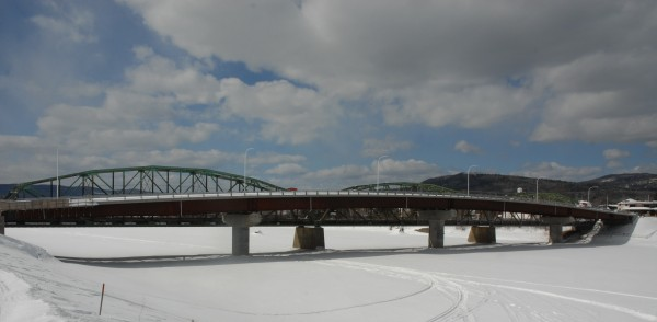The frozen St. John River passes through Fort Kent and around the pilings of the old international bridge and the new bridge under construction. Officials are keeping an eye on the additional pilings in case ice starts to jam up there this spring.