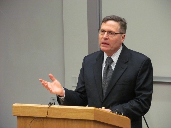 Joseph McDonnell, dean of the University of Southern Maine's Muskie School of Public Service, addresses graduate students and faculty members Tuesday night in an auditorium on the Portland campus. Students and faculty in the school's public policy and management program have expressed concerns about cuts to the program.