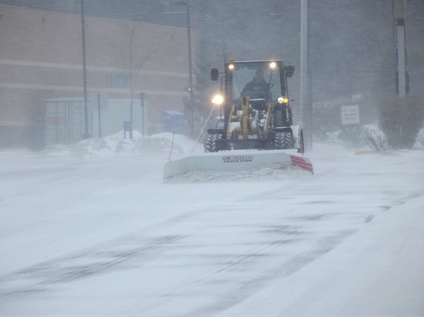 A loader equipped with a plow begins working in windy, swirling snow at the Hannaford grocery store in Machias as blizzard conditions moved into the region Wednesday morning.