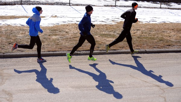 Ellworth High School long-distance runners Dan Curts (left) and Braydan Beardsley (right) train with Husson University graduate student Matt Homich in Ellsworth Monday.