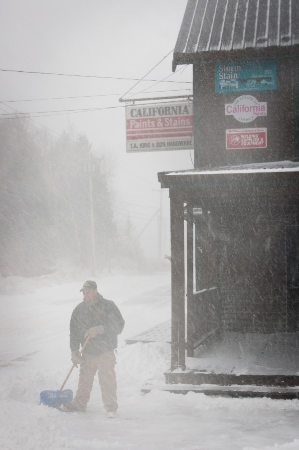 An employee shovels outside of T.A. King Hardware in Jonesport Wednesday afternoon during a snowstorm that is expected to bring several inches to the coastal areas of the state.
