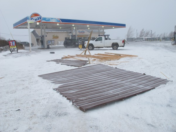 A shed roof that covered an air-conditioning unit behind the On The Run convenience store on Route 3 in Ellsworth lies in the parking lot in front of the store Wednesday after high winds ripped it into the air. The airborne roof sailed over the store and gas station canopy before striking a parked, unoccupied vehicle in the parking lot and smashing its windshield.