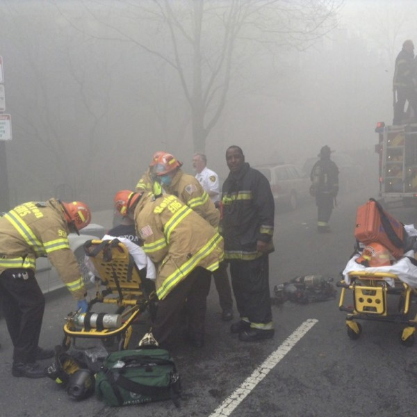 Firefighters tend to an injured person as they battle a nine-alarm blaze in Boston's Back Bay neighborhood on Wednesday.
