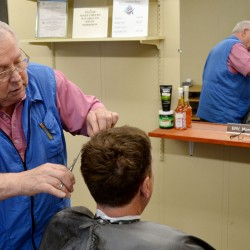 Erv Morrison cuts a customer's hair at his barber shop on Hammond Street in Bangor. Morrison opened the shop a year ago; he had cut hair in Orono for 50 years before moving to Bangor. He sweeps the floor after each hair cut; cleanliness is an important business practice for the 77-year-old barber.