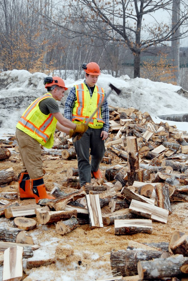 Brewer High School student Jonathan Bouchard (right) watches as student Michael Maybury swings a maul and splits firewood behind the school in mid-March.