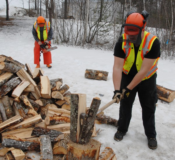 As Brewer High School teacher Mark Savage checks an Oregon chainsaw in the background, student Dempsey Oliver of Clifton swings a maul to split firewood behind the school in mid-March.