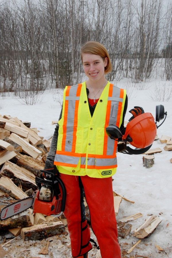 Michela Jamison of Clifton holds her logger's safety helmet and an Oregon chainsaw after cutting bolts of stove-length firewood from maple logs spread behind Brewer High School.
