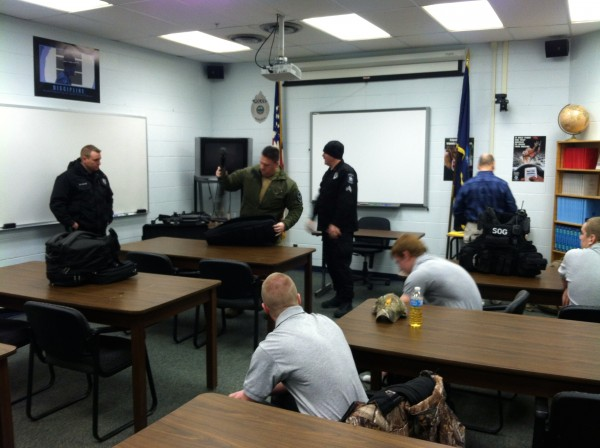 "IMG-2675: MDOC security staff setting up ""show-and-tell"" equipment as CATC Law Enforcement students are showing up for class. Standing L-to-R: Correctional Officer - K9 Handler Corporal Brian Donahue, Special Operations Group Commander Sergeant Mark Clevette, and Correctional Officer - K9 Handler Richard Greene."