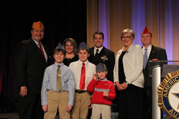 From left, Joseph Gladden, Sons of The American Legion national commander;  Sarah Smiley; Lt. Cmdr Dustin Smiley; American Legion Auxiliary National President Nancy Brown-Park; American Legion National Cmdr. Daniel M. Dellinger. In the front, Owen, Ford and Lindell Smiley are wearing their Sons of The American Legion caps.