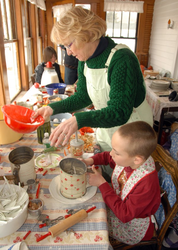 Judith Frost Gillis of Orrington shows a boy how to shift flour at the Curran Homestead Living History Farm & Museum. As part of the March 22 Maple Festival and Irish Celebration, Gillis taught children how to process foods with kitchenware dating from the 1930s and 1940s.