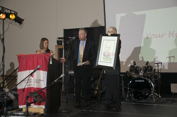 Anchors Lindsey Mills and Craig Colson present a Distinguished Service Award in the form of a caricature to Tom Brown, who also chaired the event.