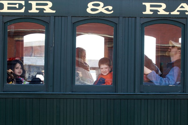 Jason McCoy (right) of New Mexico takes a steam train ride with his children Juian, 5, (center) and Sierra, 8, at the Maine Narrow Gauge Railroad Co. & Museum in Portland on Saturday.