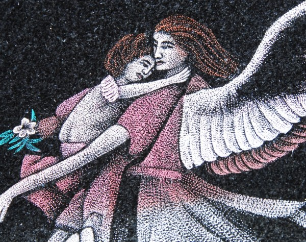 This image of an angel carrying a child was etched on black granite. This etching has been colored.